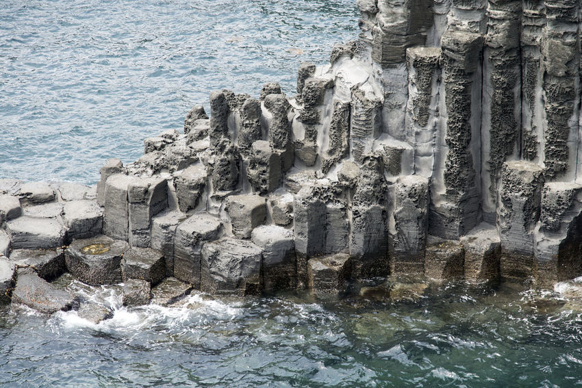view of columnar joints (jusangjeolli) at Jungmun Tourism Complex in Jeju Island, South Korea Beauty In Nature Close-up Columnar Joints Day JEJU ISLAND  Jungmun Tourism Complex Jusangjeolli Motion Nature No People Outdoors Rock - Object Sea Seaside Water Wave