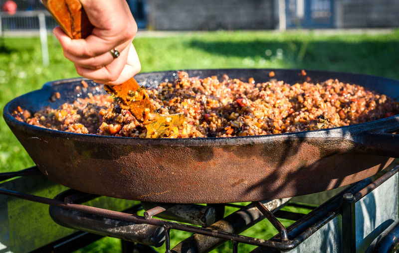 Close-up of man preparing food on barbecue grill in yard