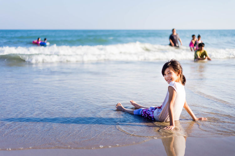 Portrait of smiling cute girl sitting on shore at beach
