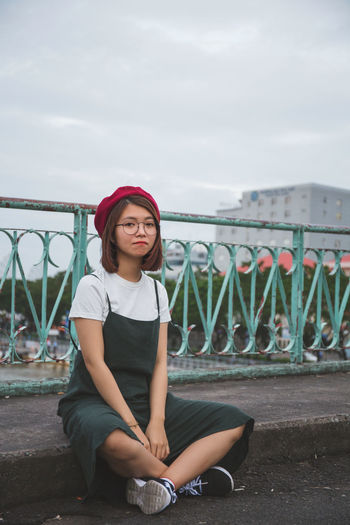 Portrait of young woman sitting on footpath in city against cloudy sky