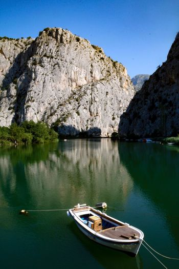 The boat EyeEm Selects Water Nautical Vessel Transportation Mode Of Transportation Beauty In Nature Mountain Scenics - Nature Sky Nature Tranquility Lake Clear Sky Day No People Reflection Tranquil Scene Rock Tree Plant Outdoors
