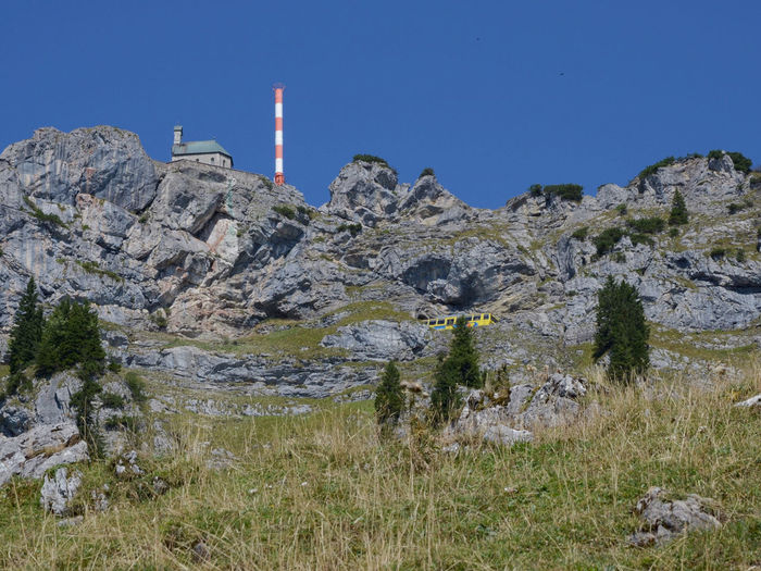 Low angle view of sternwarte wendelstein on rocky mountain against clear blue sky