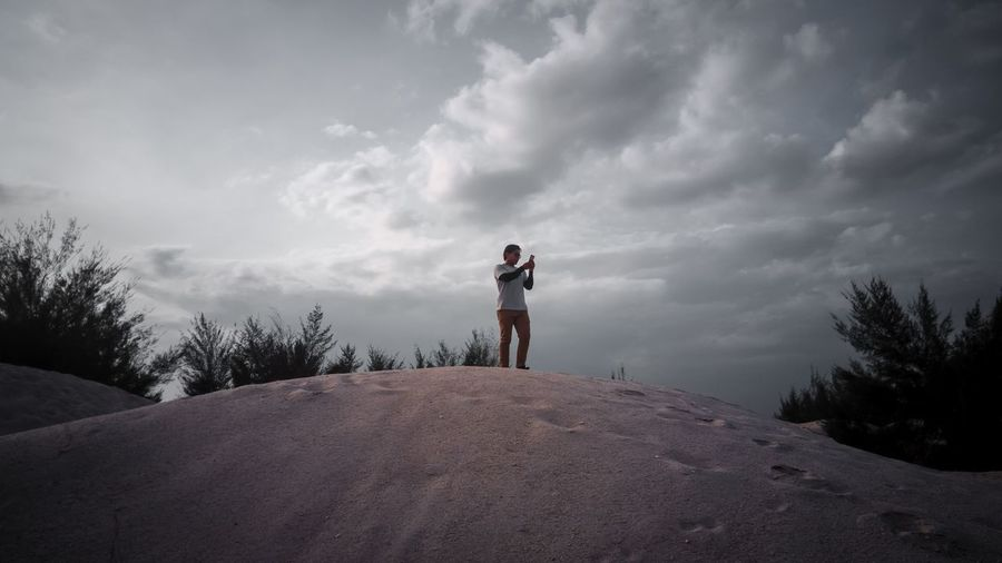 Man using mobile phone while standing on sand against sky