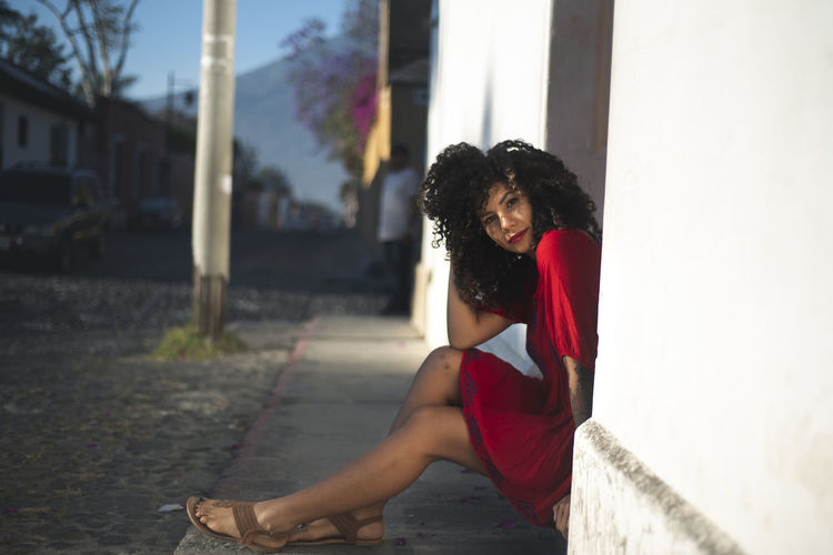 Red Dress Architecture Beautiful Woman Building Exterior Built Structure Casual Clothing Curly Hair Day Fashion Full Length Hair Hairstyle Leisure Activity Lifestyles One Person Outdoors Real People Side View Sitting Women Young Adult Young Women