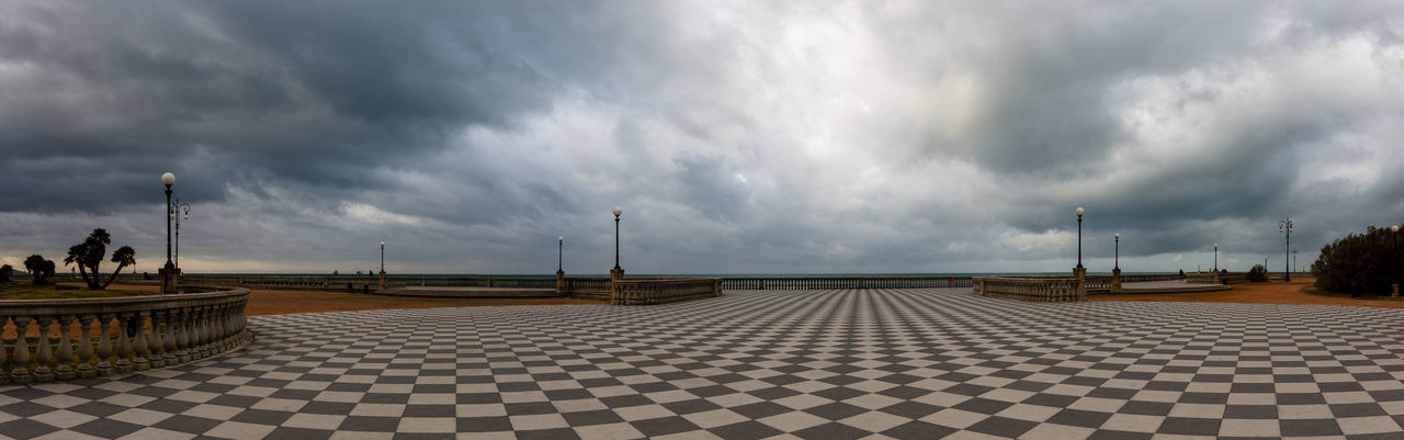 Panoramic view of street against cloudy sky