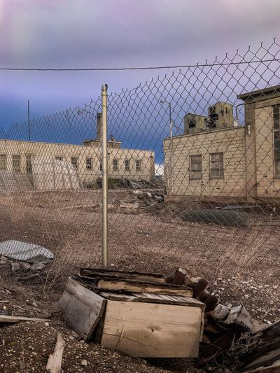 Abandoned building seen through chainlink fence