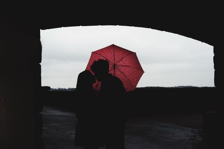 Rear view of silhouette couple standing against sky