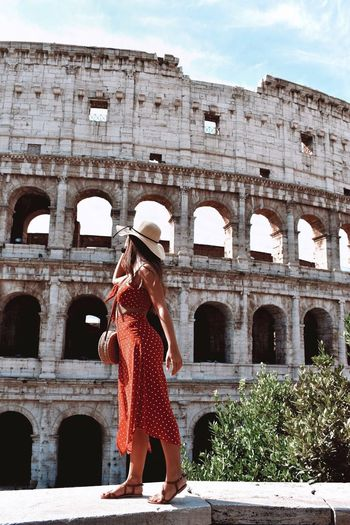 Full length of woman in dress standing on retaining wall against coliseum during sunny day