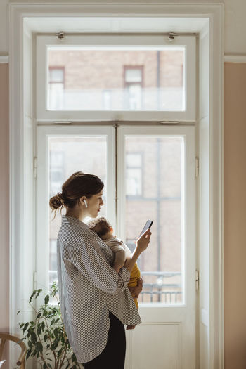 Woman holding mobile phone while standing on window