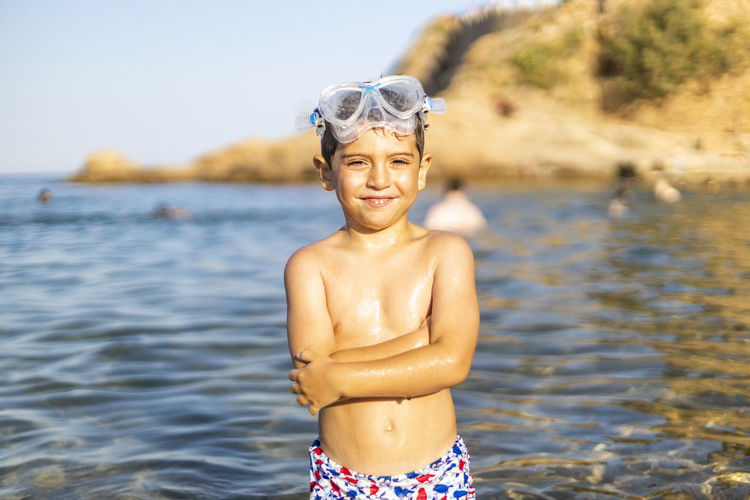 Portrait of smiling shirtless boy standing at beach