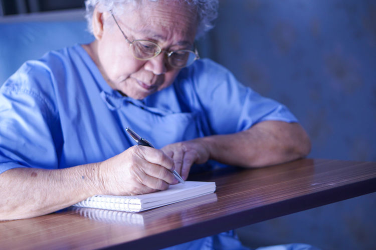 Senior man writing in book on desk at home