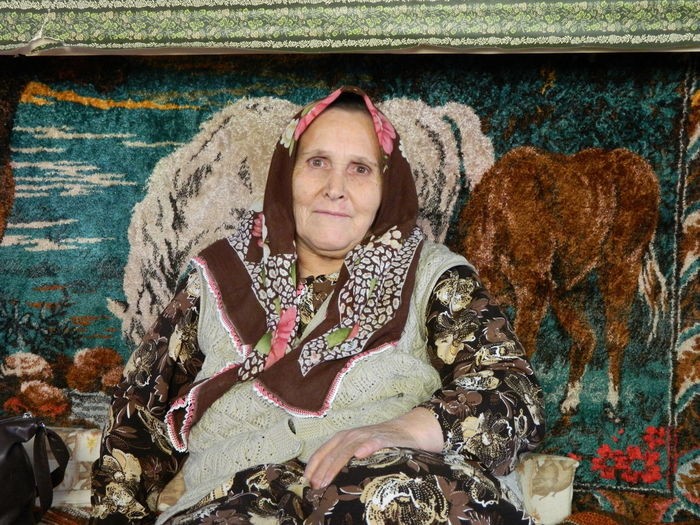 Portrait Of Senior Woman Sitting Against Paintings On Wall