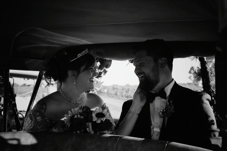 Smiling bride and groom sitting in car