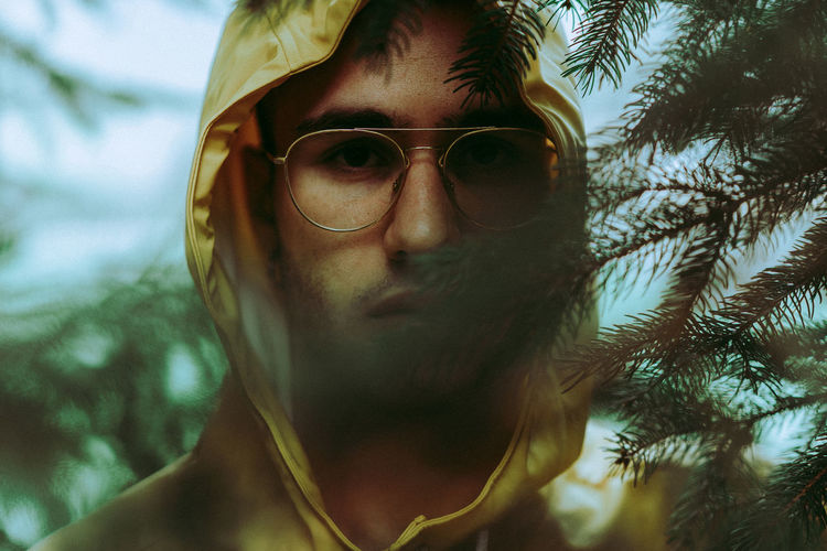 Portrait of young man wearing eyeglasses by pine tree