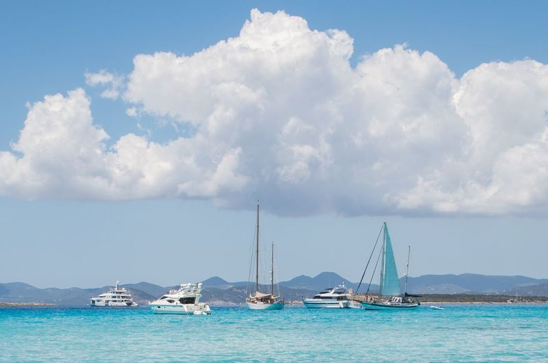 Sailboats And Yachts Sailing In Sea Against Sky