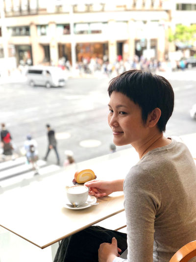 High Angle View Of Mature Woman Having Coffee In Cafe