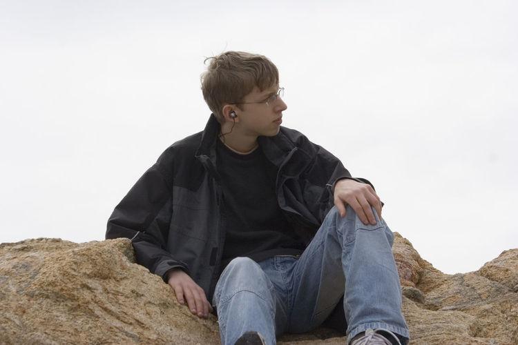 Teenage Boy Sitting On Rocks Against Clear Sky