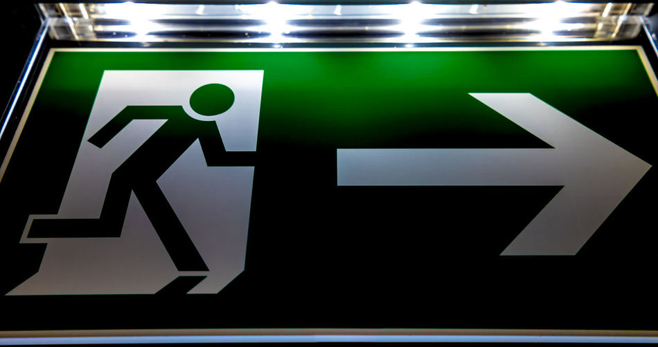 Exit Sign. Communication Illuminated Guidance Symbol Sign Indoors  Arrow Symbol Directional Sign No People Text Information Information Sign Direction Emergency Exit Lighting Equipment Close-up Representation Green Color Exit Sign Information Symbol Western Script Color Close Up Technology