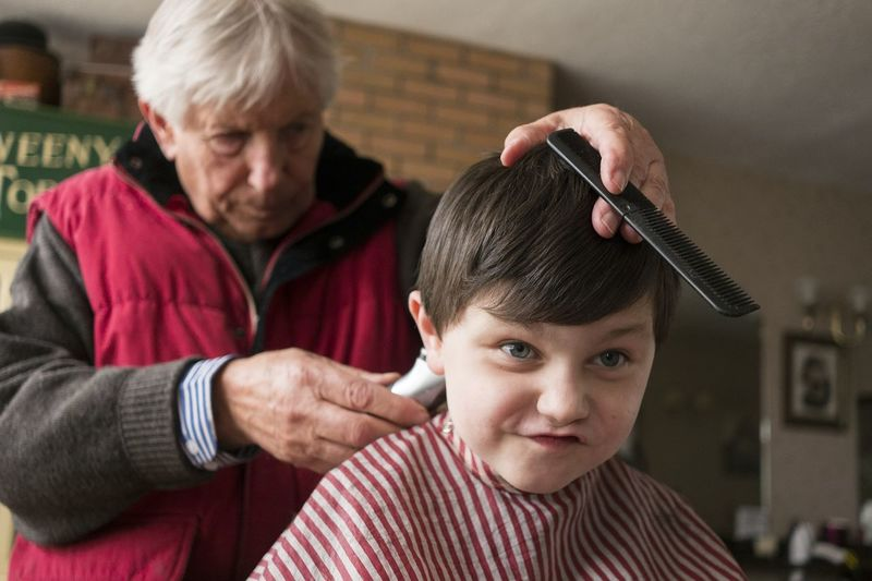 Close-up of a boy getting a haircut at the barber