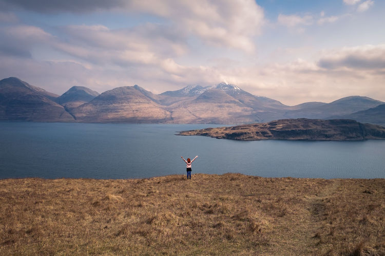 Young girl standing by lake against highland scenery