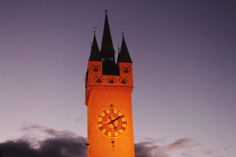 Low angle view of clock tower against orange sky