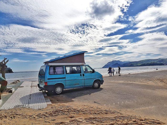 Van on beach against sky