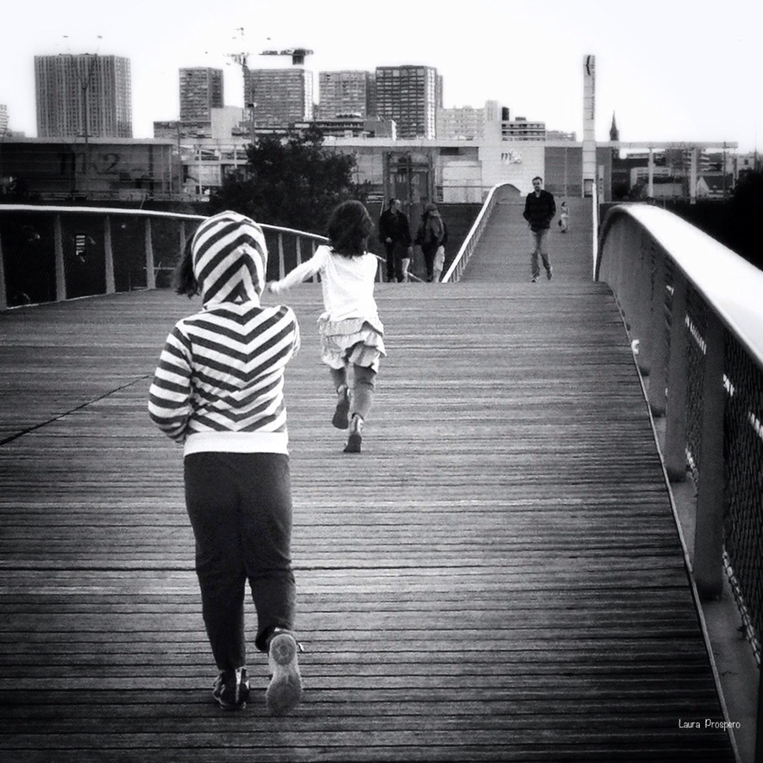 full length, lifestyles, rear view, walking, togetherness, leisure activity, men, built structure, building exterior, architecture, casual clothing, boys, city, bonding, childhood, city life, railing