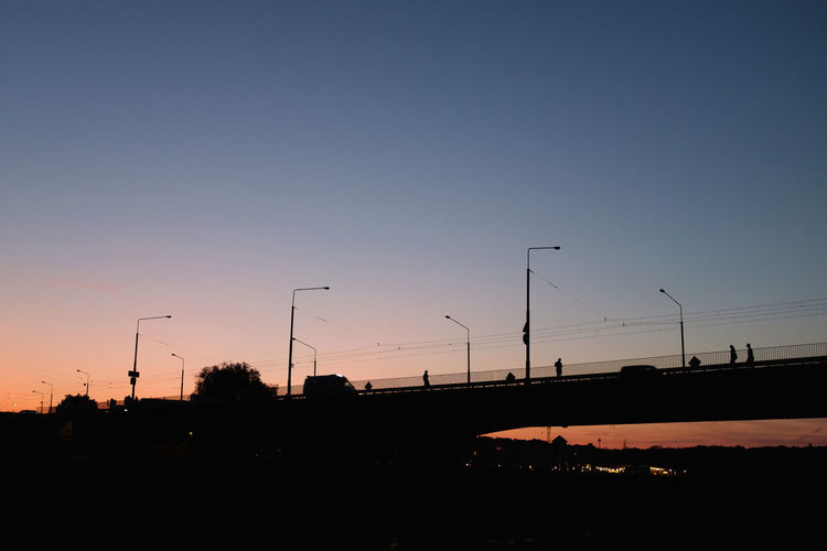 Silhouette street against clear sky at sunset