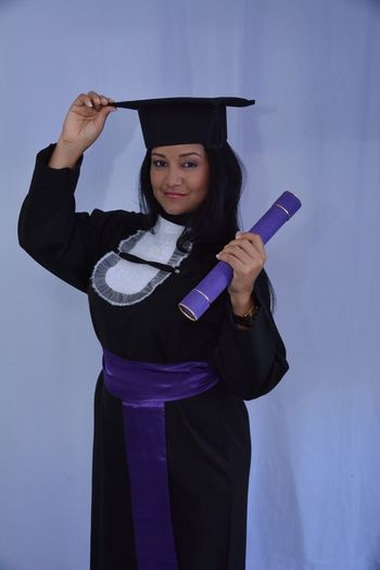 Portrait Of Woman Wearing Graduation Gown Against White Background