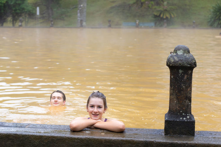 Teen girl and young man swimming in a mineral thermal pool in terra nostra park at furnas, azores