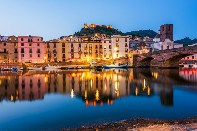 Reflection of illuminated buildings in river against clear blue sky