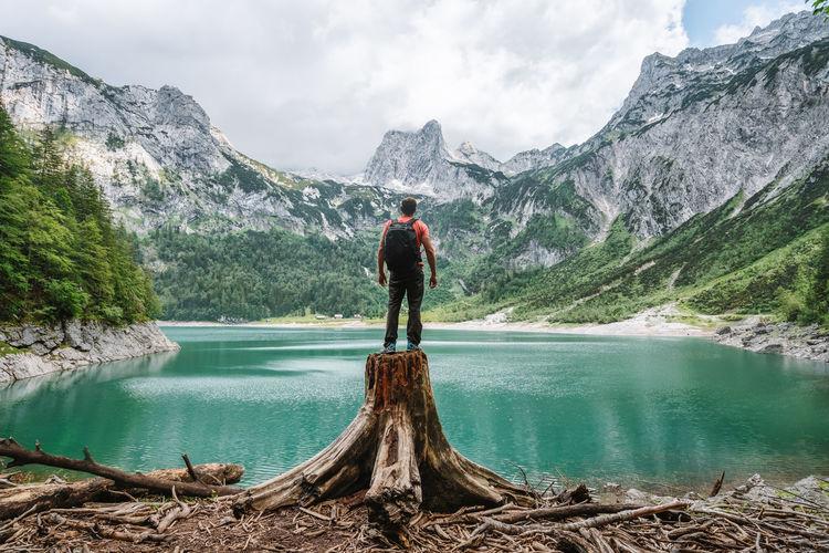 Woman looking at lake against mountain range