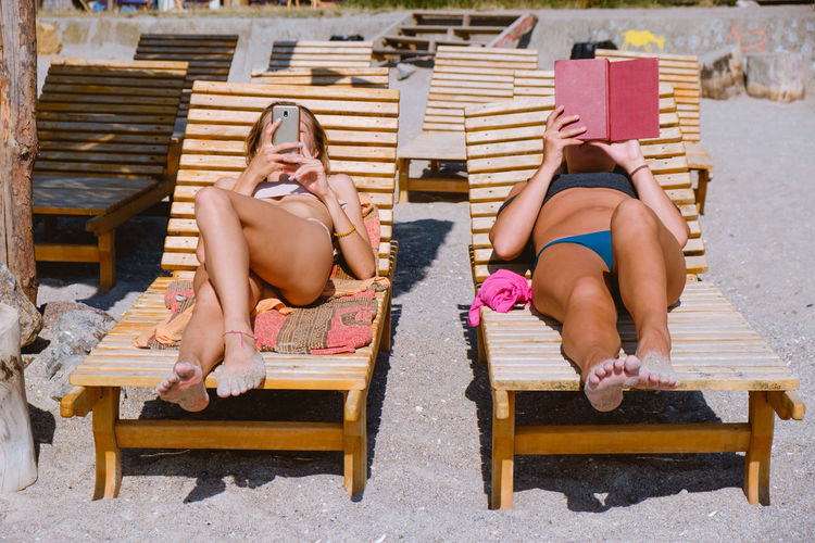 Two beautiful girls lying on the benches on the sea side. One woman is reading something in a book, another one is reading from a smartphone. Beach Life Summer Summer Views Chilling Sandy Beach Sunny Day Woman Vaccation Relaxing Relaxing Moments Sexywomen Film Photography Vibrant Color Warm Colors Warm Light Feminine  Femininity Reading A Book Reading Technology Technology I Can't Live Without Technology Everywhere Smart Phone Comparison Different Perspective Lounge Chair Holiday Young Adult Bench