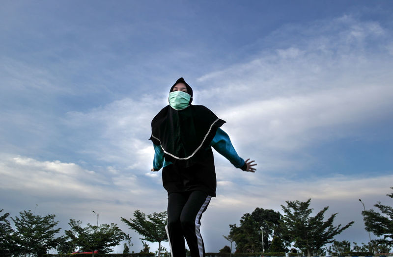 Low angle view of woman wearing mask against sky