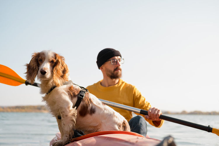 Man sitting in kayak with dog in sea
