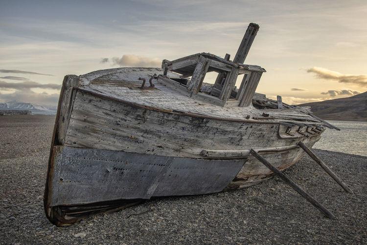 Abandoned ship on beach against sky