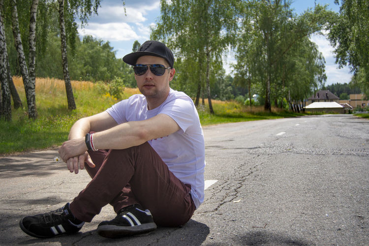 Young man wearing sunglasses sitting on road against trees