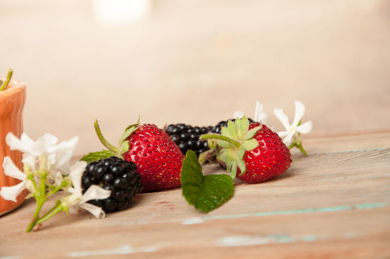 Close-up of strawberries and blackberries on wooden table