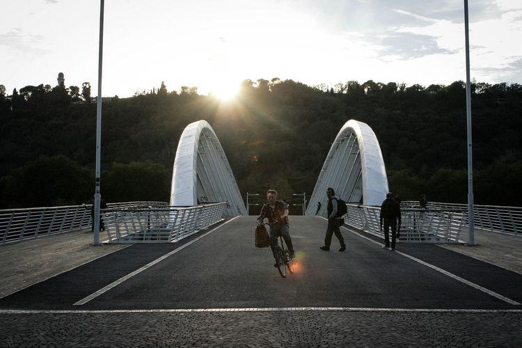 People walking on footpath by footbridge against sky