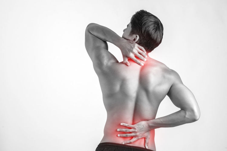 Backache Hand Healthcare And Medicine Human Back Human Body Part Indoors  Lifestyles Men One Person Pain Physical Injury Rear View Red Shirtless Standing Studio Shot Touching Waist Up White Background
