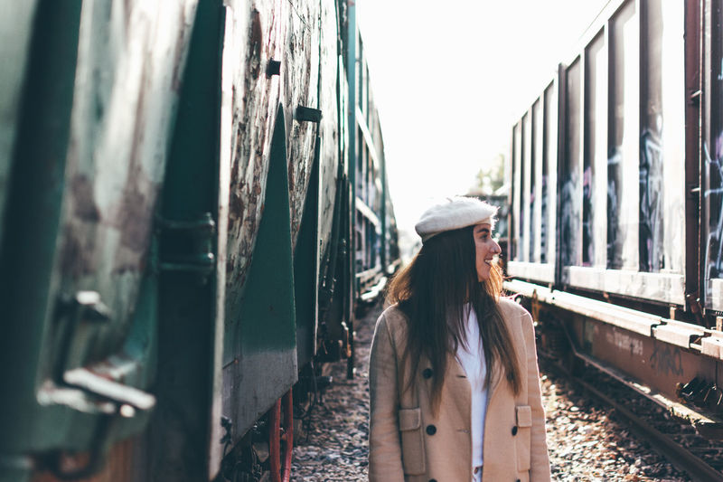 Smiling woman standing by trains on railroad track