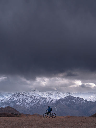 Man with bicycle against mountains and stormy clouds during winter