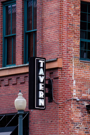 lit tavern sign against a brick building Brick Wall Wall Craftsmanship  Retro Access Bar Aged Structure Relic Building Old Rugged Strong Rustic Architectural Solid Ancient Stronghold Tavern  Ornate Bricks Design Pub Weathered Antique Vintage Medieval Architecture Façade Square Trendy Space Red Sign Texture Restaurant Menu Background Lunch Text Brick Wood City Neon Lamp Post Vertical Windows