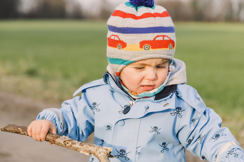 Cute baby girl wearing warm clothing standing in park