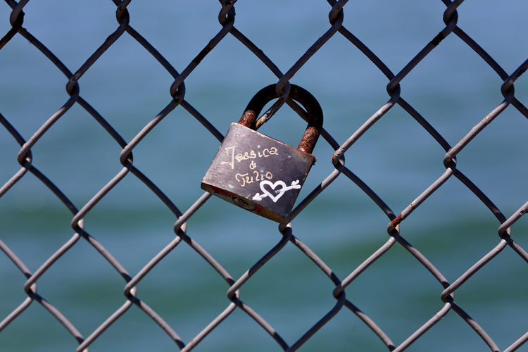 Close-up of padlocks on chainlink fence