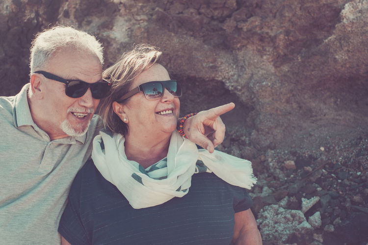 Smiling Senior Couple Standing By Rock Formation