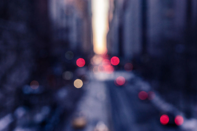 Defocused image of lights on street amidst buildings