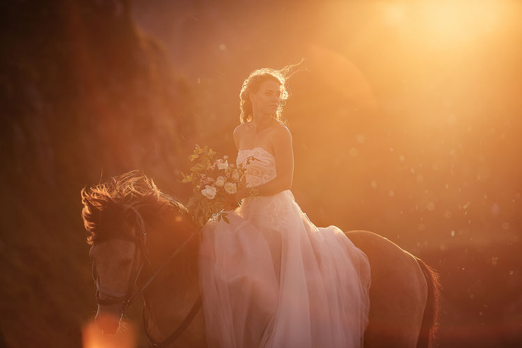 Beautiful bride holding bouquet sitting on horse during sunset