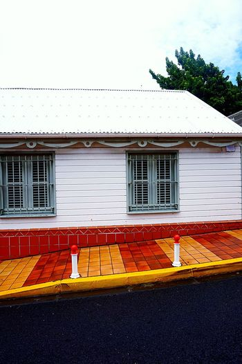Colors after the rainfall Architecture Architecture Facade Asphalt Caribbean Colorful Colors Diagonal Empty Places Exterior Façade Geometric Shapes House Martinique Road Roof Sidewalk Street Photography Streetphotography Textured  Urban Wall Wall - Building Feature White Windows Wood