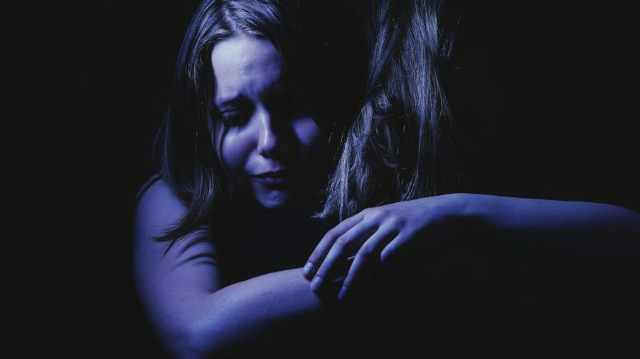 Close-up of depressed woman crying by holding friend against black background